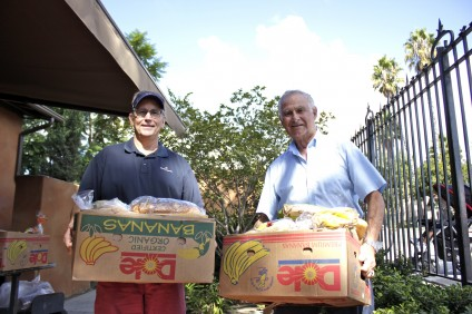 David Bordages and Ray Poncé help oversee food distribution to struggling families through Mission Basilica's Serra's Pantry & Outreach Ministries. Photo by Brian Park