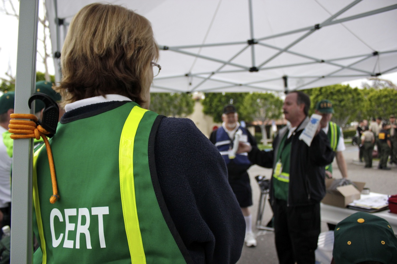Volunteers from the Community Emergency Response Team listen to instructions before the 55th Swallows Day Parade. Photo by Brian Park