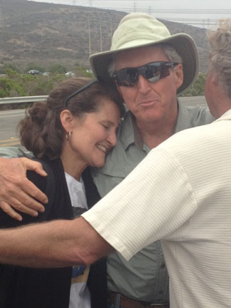 Laurie Headrick of San Clemente and Steve Netherby embrace in celebration of the closure of the San Onofre Nuclear Generating Station. Photo by Jim Shilander