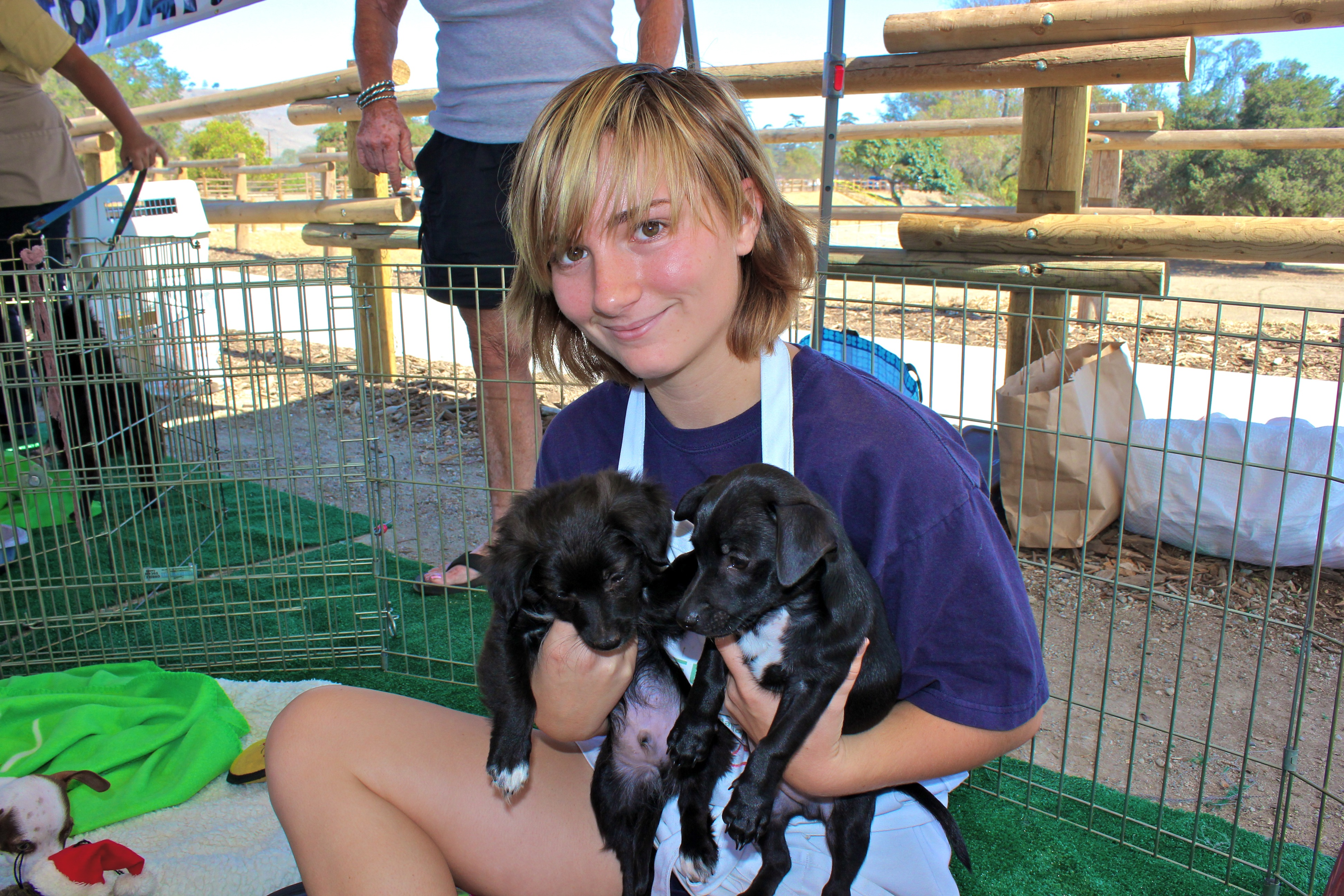 Codi Hall, a volunteer with the Greendog Foundation, holds two puppies that were available for adoption during the grand opening of the Dr. Joe Cortese Dog Park. Photo by Brian Park