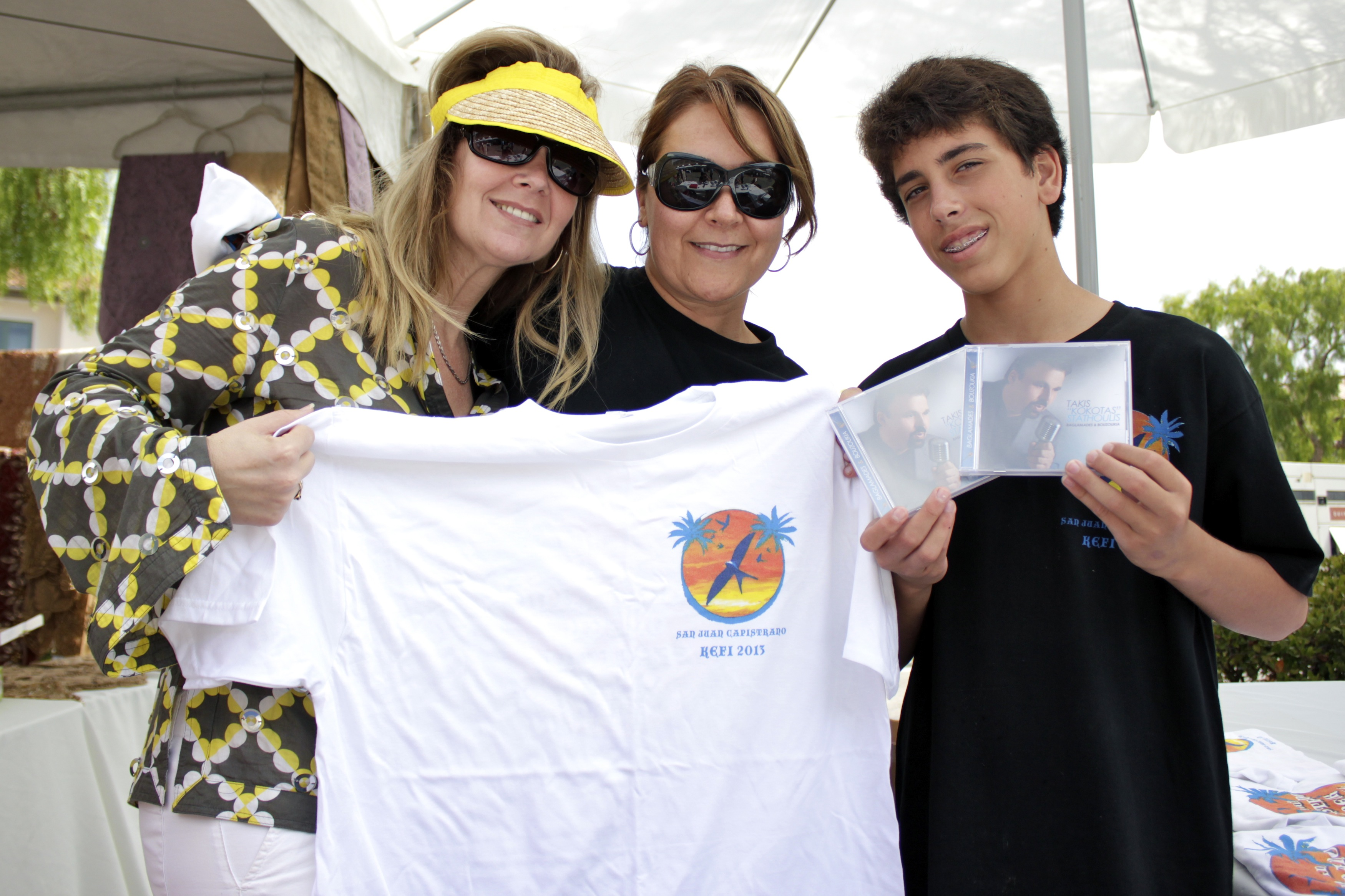 (From L to R) Jennifer Fleming, Sylvia Stewart and John Stavrov show off T-shirts and CDs on sale during the Greek Festival. Photo by Brian Park