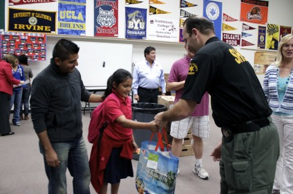 San Juan Capistrano Sheriff's Deputy Felipe Martinez hands San Juan Elementary School fourth-grade student Kayla Teliz a bag of Thanksgiving food items as Teliz's father, Miguel Aguilar, looks on. Photo By Brian Park