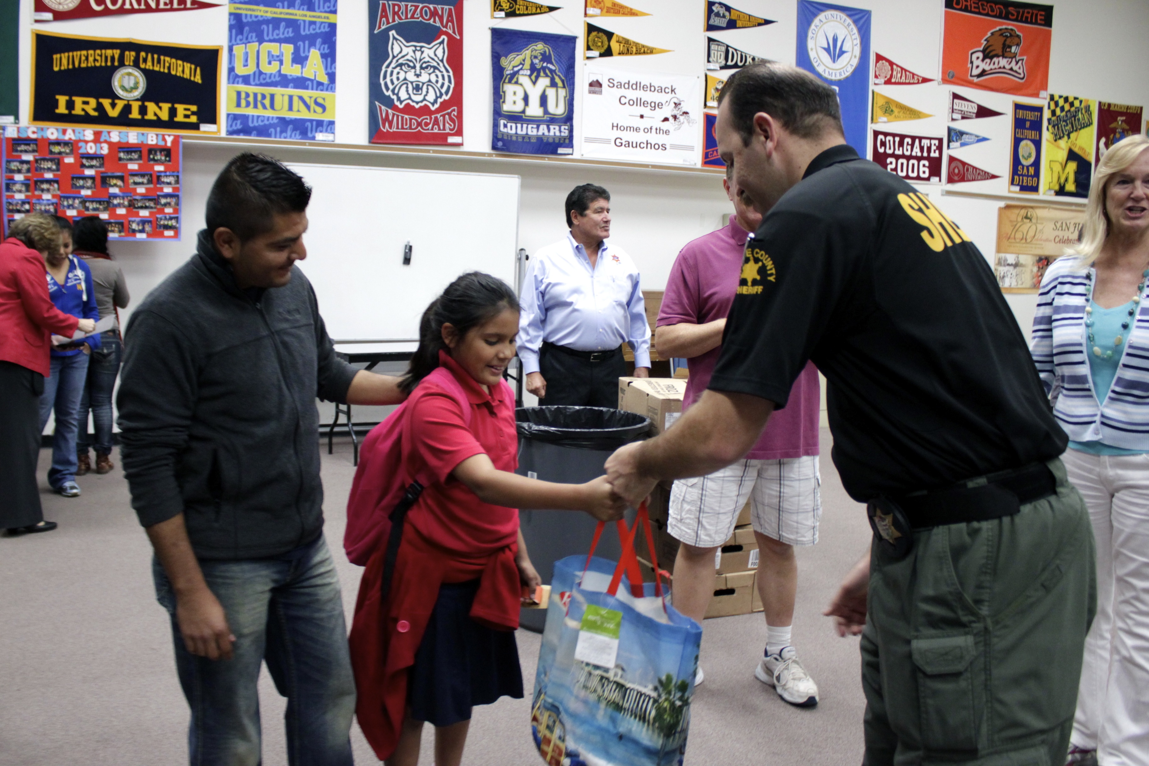 San Juan Capistrano Sheriff's Deputy Felipe Martinez hands San Juan Elementary School fourth-grade student Kayla Teliz a bag of Thanksgiving food items as Teliz's father, Miguel Aguilar, looks on. Photo By Brian Park