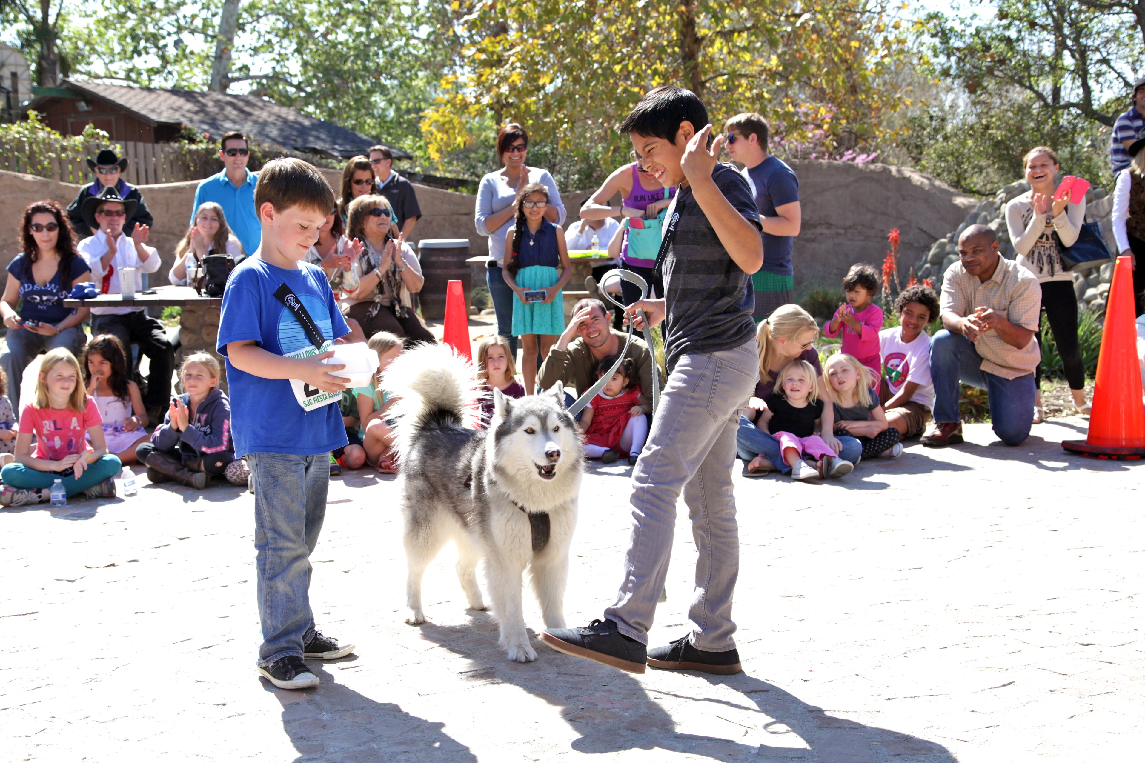 Nathan Grazioli (left) and Hector Reyes prepare to perform a trick with their dog, Luna. Photo by Brian Park