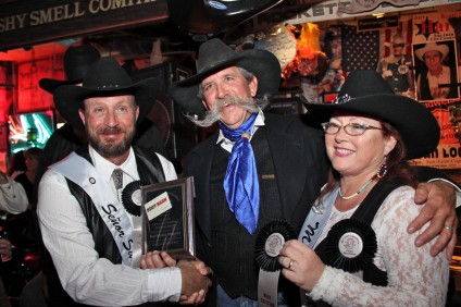 Doug Davis is awarded for his mustache by Fiesta Association dignitaries James and Deborah Valgean. Photo by Brian Park