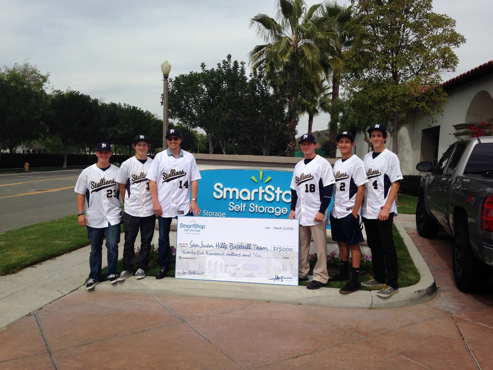 San Juan Hills High School baseball players pose for a photo beside a check for $25,000, donated by Ladera Ranch-based SmartStop Self Storage. The money will go toward building and installing the team's new scoreboard. Courtesy photo