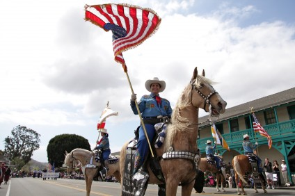 Holding an American flag, a rider from the Merced County Sheriff Posse stops in front of the VIP section at the 56th Swallows Day Parade. Photo by Brian Park