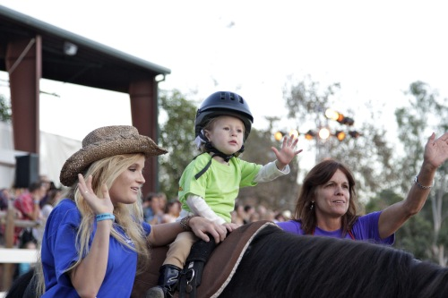 A young J.F. Shea Therapeutic Riding Center client demonstrates her riding skills with the help of volunteers at the center's annual barbeque on Sept. 27. Photo: Brian Park
