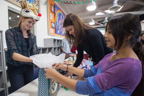 Maddie Barkate, 13, of San Juan Capistrano, helps 11-year-old Emily Flores, also from San Juan, wrap a present for her sister at the annual Operation Holiday Homework event hosted by the Boys & Girls Clubs of Capistrano Valley in San Juan Capistrano on Dec. 13.