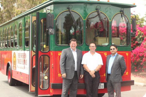 (L to R) Ralph Caldin, president of Professional Parking, Mike Caldin, supervisor/director of operations, and Mario Montenegro, chief operations officer stand with the trolley, which leased from the city of Brea, on Thursday afternoon. Photo: Eric Heinz
