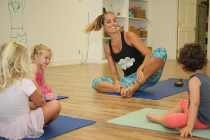 Grace + Zen owner and teacher Nikki Sulon does a warm up with three students during a combo ballet and yoga class. Photo: Allison Jarrell
