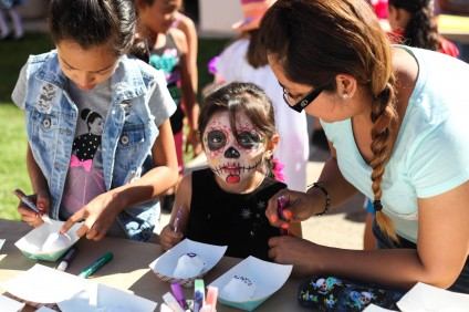 (From L to R) Kimberly Ayala, 10, Lupita Ayala, 4, and their mother, Miriam Ayala, of San Juan Capistrano, decorate sugar skulls together at the library's Dia de los Muertos celebration on Saturday. Photo: Allison Jarrell