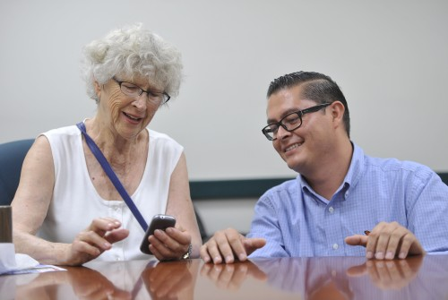 Monarch HealthCare ambassador Jose Juarez and San Juan Capistrano resident Pat Callum share a smile when Pat learns how to successfully navigate her Smart Phone. Photo: