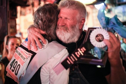 Steve Holt, winner of the 2015 Fiesta Grande Hairiest Man Contest, hugs friend and competitor Jim Curwood, former parade marshal and owner of Buy My Bikes. Photo: Allison Jarrell