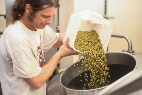 Jim Clarke, head brewer of Left Coast, adds hops to a kettle of boiling wort, which will eventually be fermented into beer.
