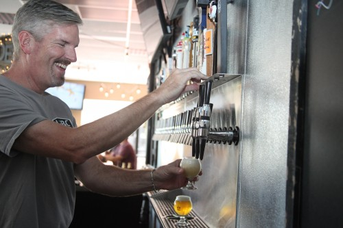 Andrew Reed, a co-owner of The BrewHouse in San Juan, pours some craft beer tasters.