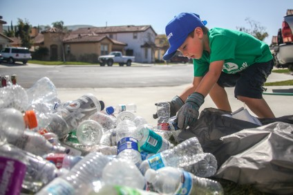 Six-year-old Ryan Hickman, founder of Ryan's Recycling, sorts through plastic bottles at his San Juan Capistrano home. Photo: Allison Jarrell
