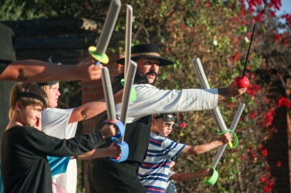 "Jim Leone teaches kids the art of sword fighting with foam swords during the opening night of the Camino Real Playhouse's adaptation of ""The Curse of Capistrano."""