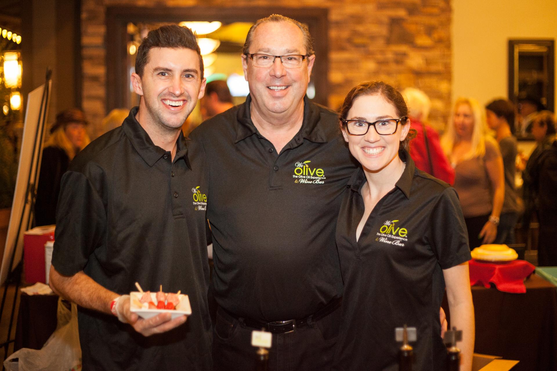 (L to R) Garrett Szubielski, Ed Szubielski, owner of We Olive & Wine Bar, and Kayla Szubielski, serve up stuffed peppadews. Photo: Alex Paris