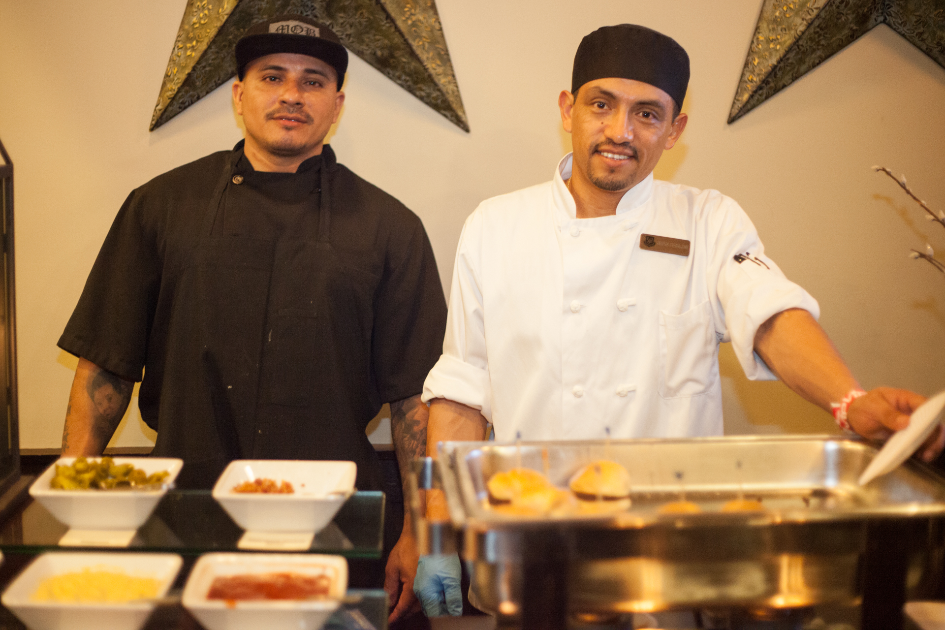 (Left to Right) Cook Tomas Garcia and chef Roberto Martinez of 19 Sports Bar and Grill serve up beef sliders. Photo: Alex Paris