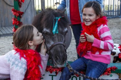 "Ruby Weeks, 7, and Molly Weeks, 5, of Irvine, giggle as they give Benny the horse a kiss as part of the J.F. Shea Center's annual ""Drive to Ride"" campaign. The sisters ride together at the center. Photo: Allison Jarrell"