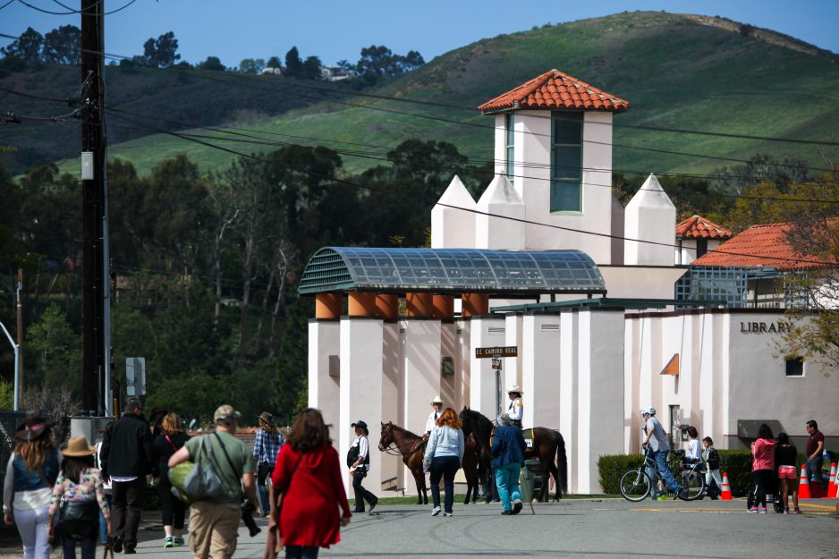 Visitors walk toward the library during last year's Swallows Day Parade. Photo: Allison Jarrell
