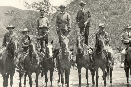 In this photo from the Willard Smith Collection, circa 1929, a group of local officials, including Orange County Supervisors Willard Smith and William Schumacher, stand on horses while inspecting the future site of the Ortega Highway. Photo: Courtesy of Orange County Archives.