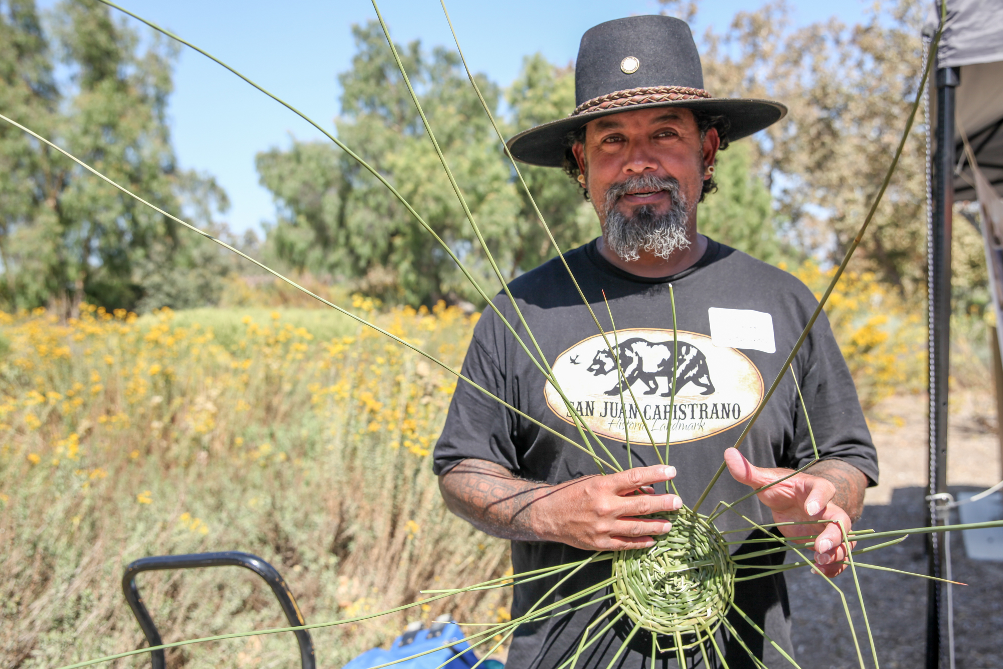 Domingo Belardes, curator of the Blas Aguilar Adobe Museum, weaves an open-work basket out of juncus. The baskets were used by the Acjachemen people for gathering roots, nuts and berries. Photo: Allison Jarrell