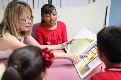 Marilynn Boyle, of San Juan Capistrano, reads to Lizette Vergara (center) Diego Prado and Miranda Rosas during the second week of a new tutoring program at the Boys & Girls Clubs of Capistrano Valley. Photo: Allison Jarrell