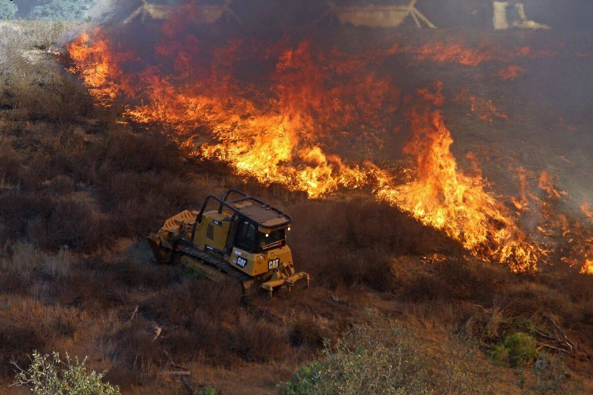 The Lilac Fire burns in San Diego in this Dec. 9 image. The fire was 100 percent contained on Dec. 16, with a total of 4,100 acres burned and 157 structures destroyed. Photo: Jeff Hall/CAL FIRE