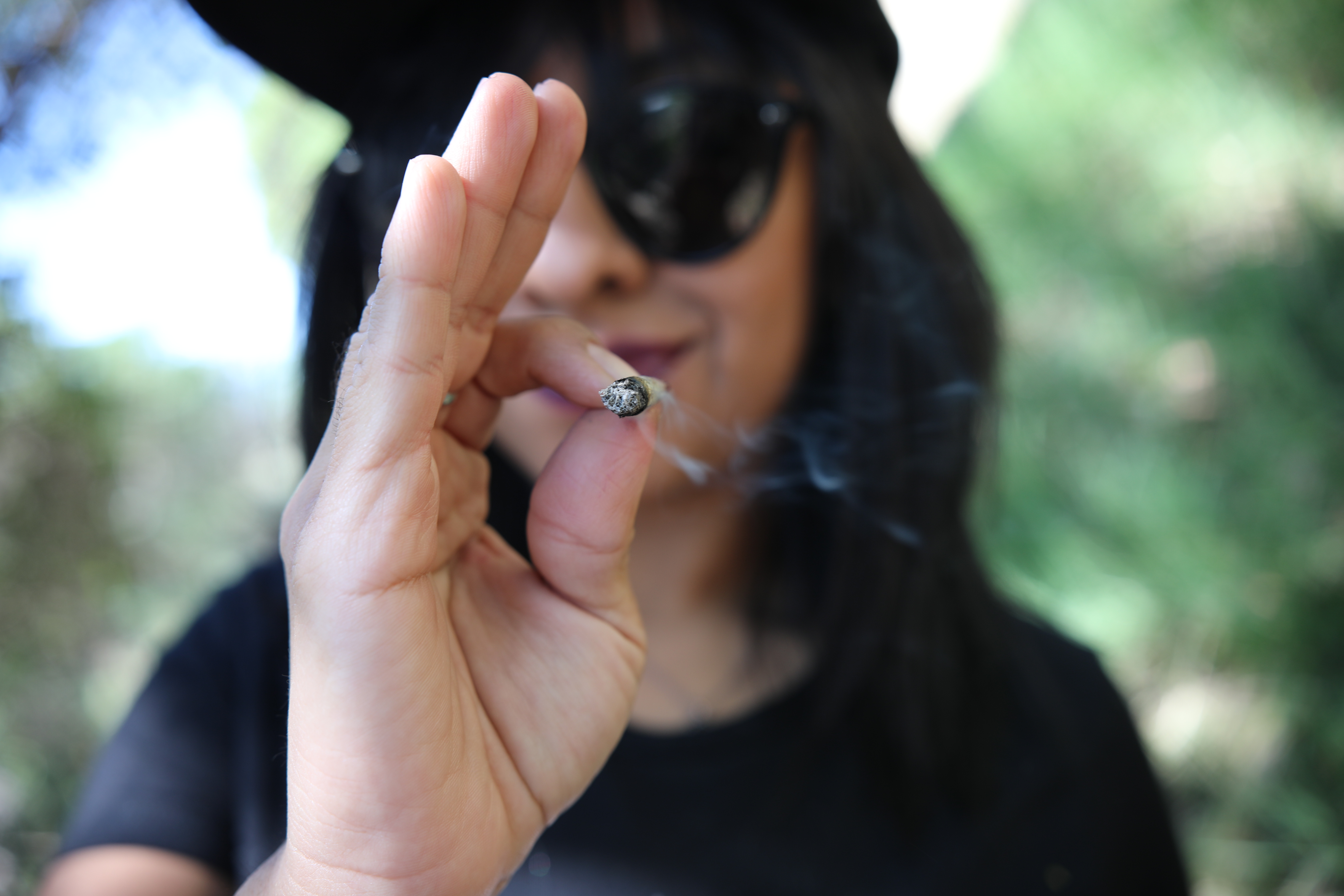"""A woman smokes from a cannabis cigarette, also known as a """"joint."""" New laws allow for personal use of recreational cannabis in California for people 21 and older, but federal laws and policies still classify cannabis in the top drug enforcement priority. Photo: Rachael Mattice"""
