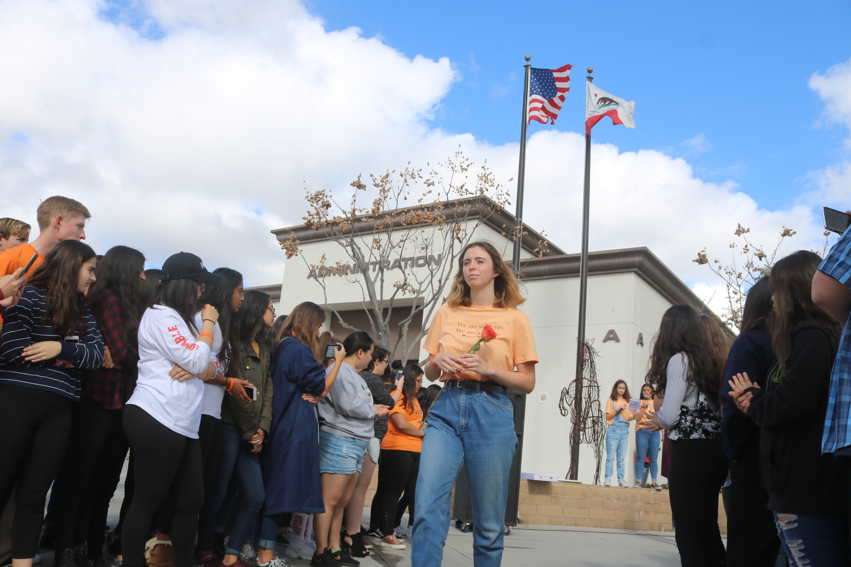 A SJHHS student carries a flower to the desk memorial for Parkland, Florida victims.