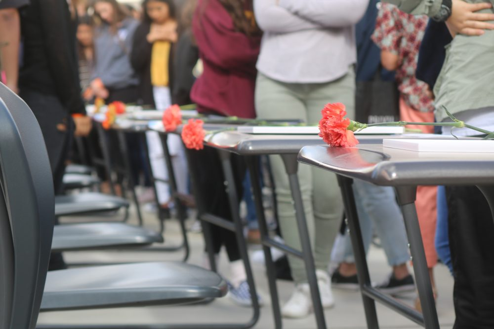 Students placed flowers on the empty desks.