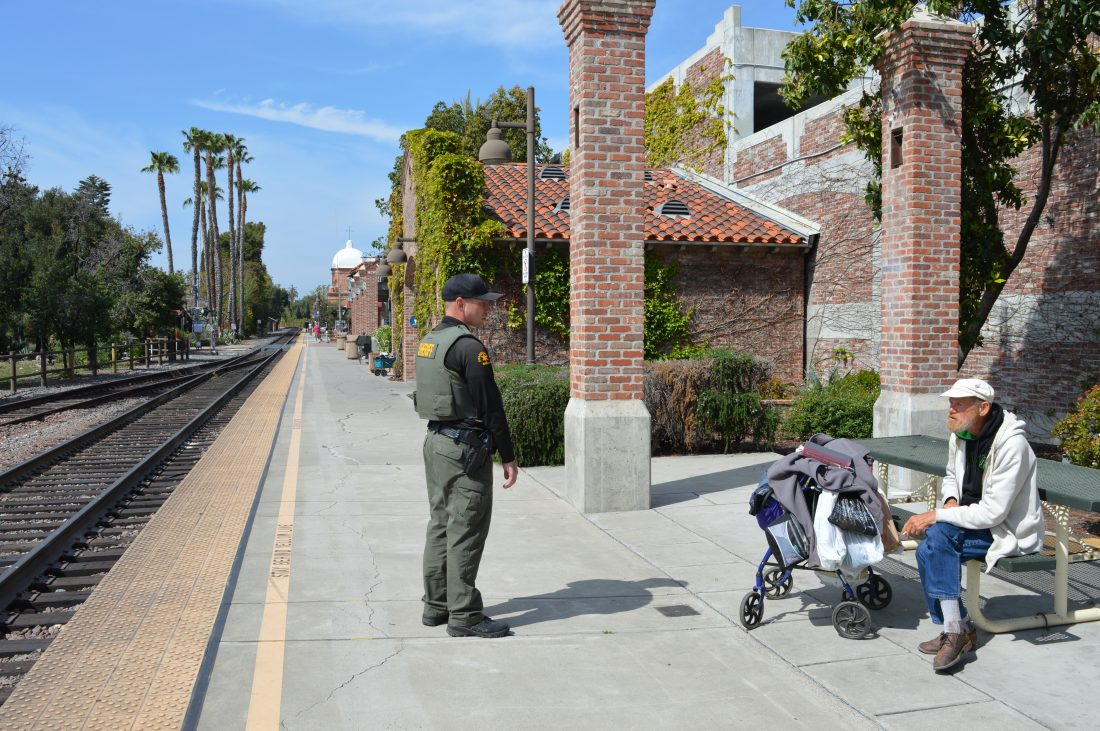 Orange County Sheriff's Department Deputy Chandler Pierce, San Juan Capistrano's homeless liaison officer, talks to Harry Bradford, a homeless man who hangs around downtown and reads books. Photo: Emily Rasmussen
