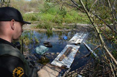 Orange County Sheriff's Department Deputy Chandler Pierce, San Juan Capistrano's homeless liaison officer, looks at trash and a make-shift bridge across the San Juan Creek. Photo: Emily Rasmussen