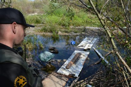Orange County Sheriff's Department Deputy Chandler Pierce, San Juan Capistrano's homeless liaison officer, looks at trash and a make-shift bridge across the San Juan Creek. Photo: Emily Rasmussen