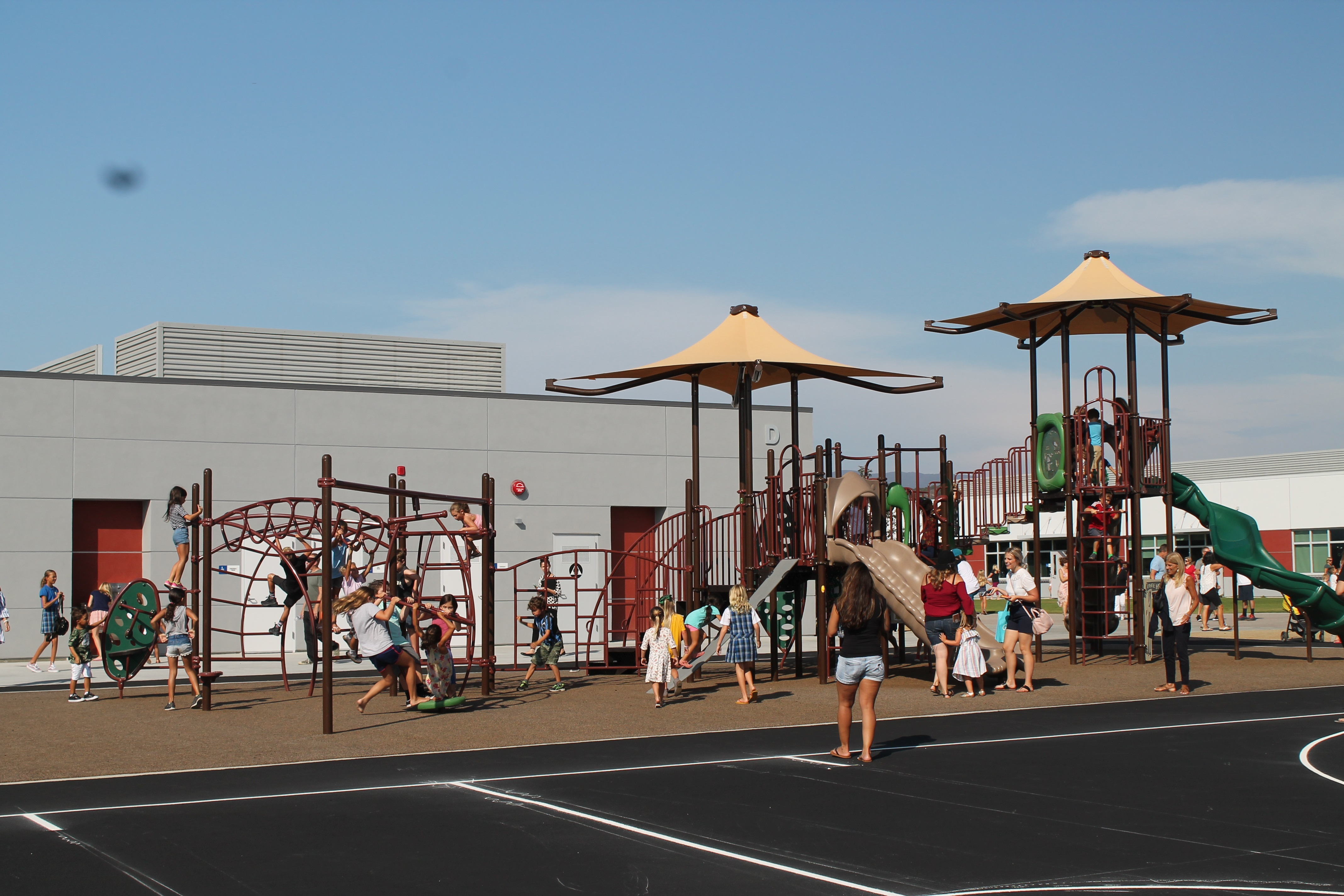 Students climb monkey bars and swing on the swingset at the playground of the new Esencia K-8 School following a ribbon cutting on Wednesday, Aug. 15. Photo: Alex Groves.