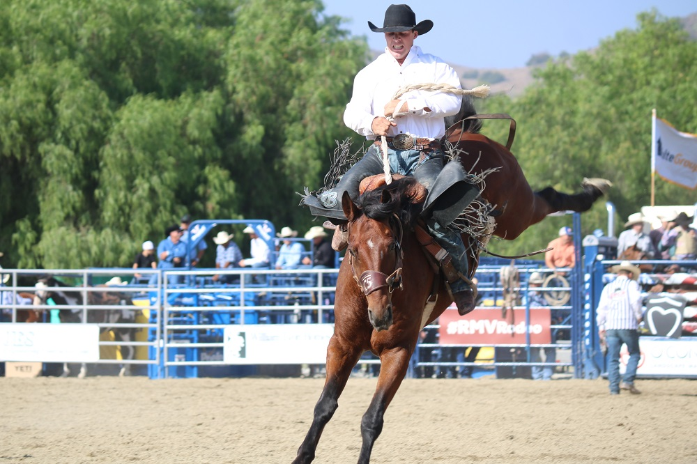 A rider holds onto a bucking horse at the 18th Annual Rancho Mission Viejo Rodeo in San Juan Capistrano on Saturday, Aug. 25.