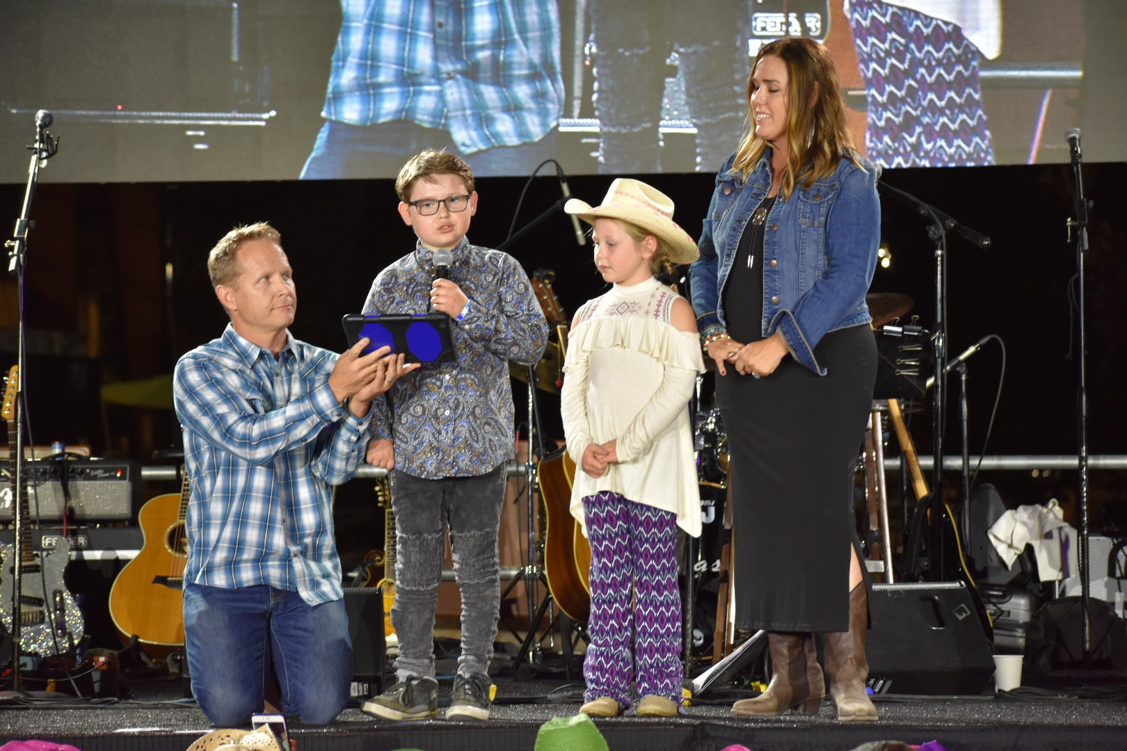Cade Spinello is joined on stage by his family as he talks about his experience as a rider at the Shea Center and how it has helped him. Photo: Alex Groves
