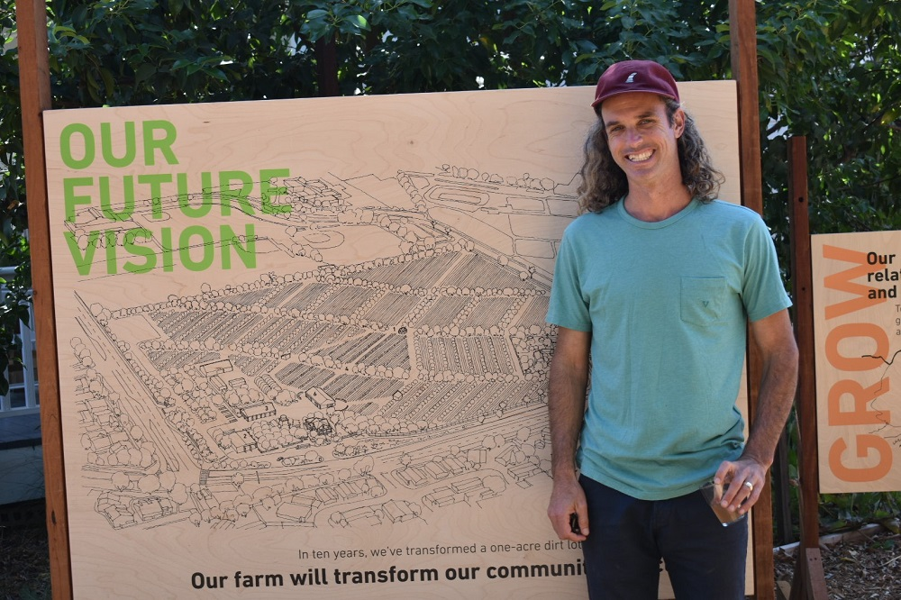 Evan Marks stands next to a sign that shows plans for the neighboring Kinoshita Farm Site. Photo: Alex Groves