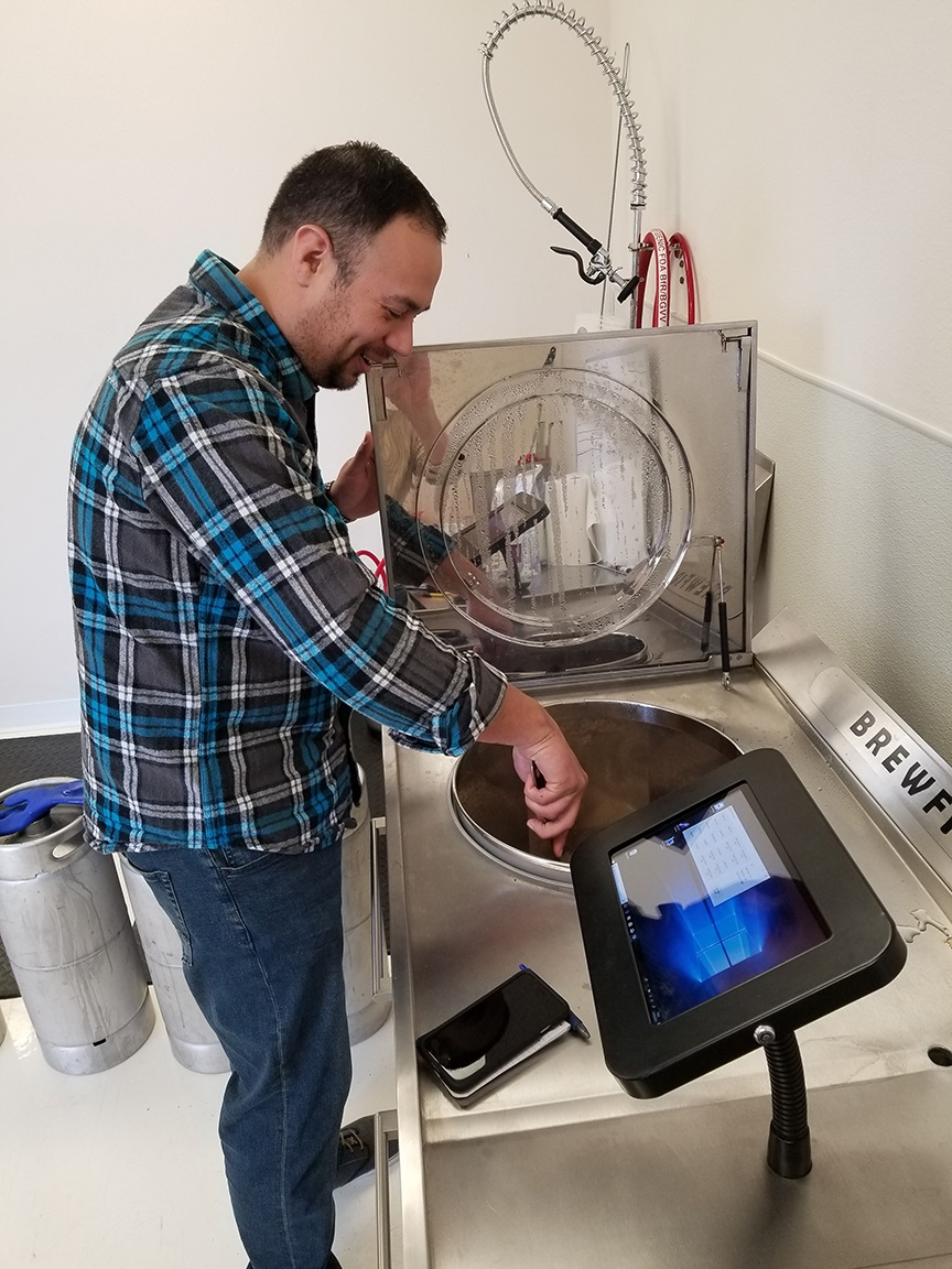 Showroom manager Alan Soran looks over the brewing beer inside one of BrewFirst's machines in their San Juan Capistrano showroom on Thursday, Sept. 13. Photo: Courtesy of BrewFirst.