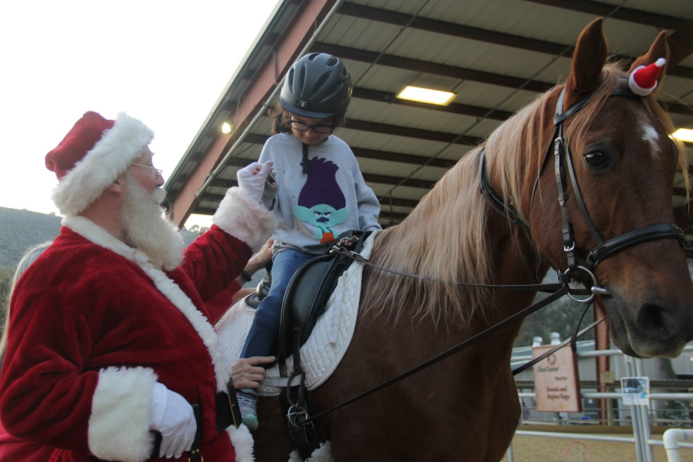 Alyna Tapia, 8, meets Santa Claus during her hippotherapy session at the J.F. Shea Riding Center on Tuesday, Dec. 11. Shea Facilities Manager Phil Dunn dressed as Santa as part of the center's Rider Recognition Week in which the children who receive treatment are given awards commemorating their progress over the latest rehabilitative session. Photo: Shawn Raymundo