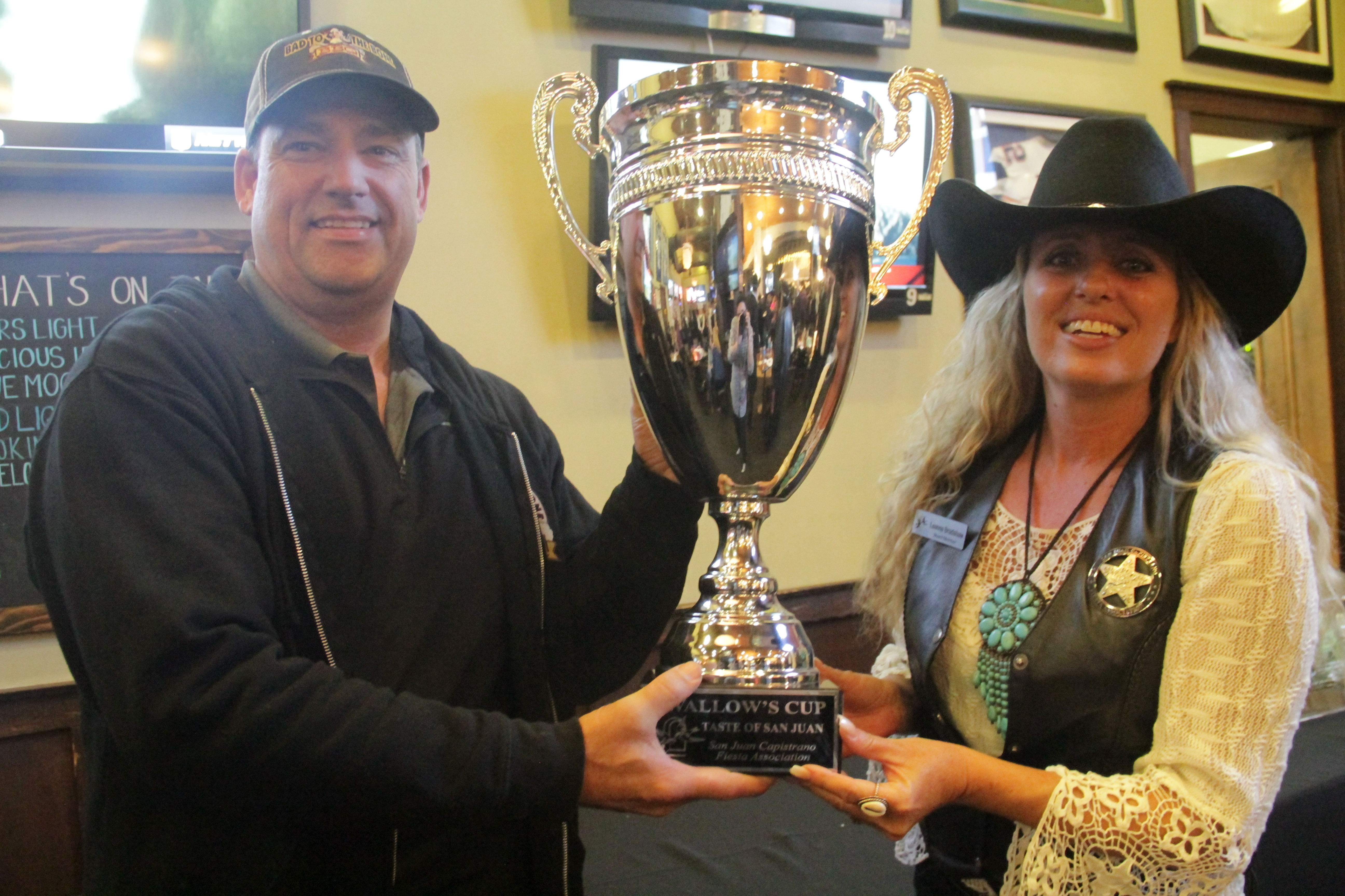 After receiving the most overall votes from guests at the Taste of San Juan on Thursday, Jan. 31, Marty Wells, owner of Bad to the Bone BBQ, displays the Swallow's Cup with the help of Fiesta Association Board Member Leanna Bradshaw, who was in charge of organizing the annual event. Photo: Shawn Raymundo