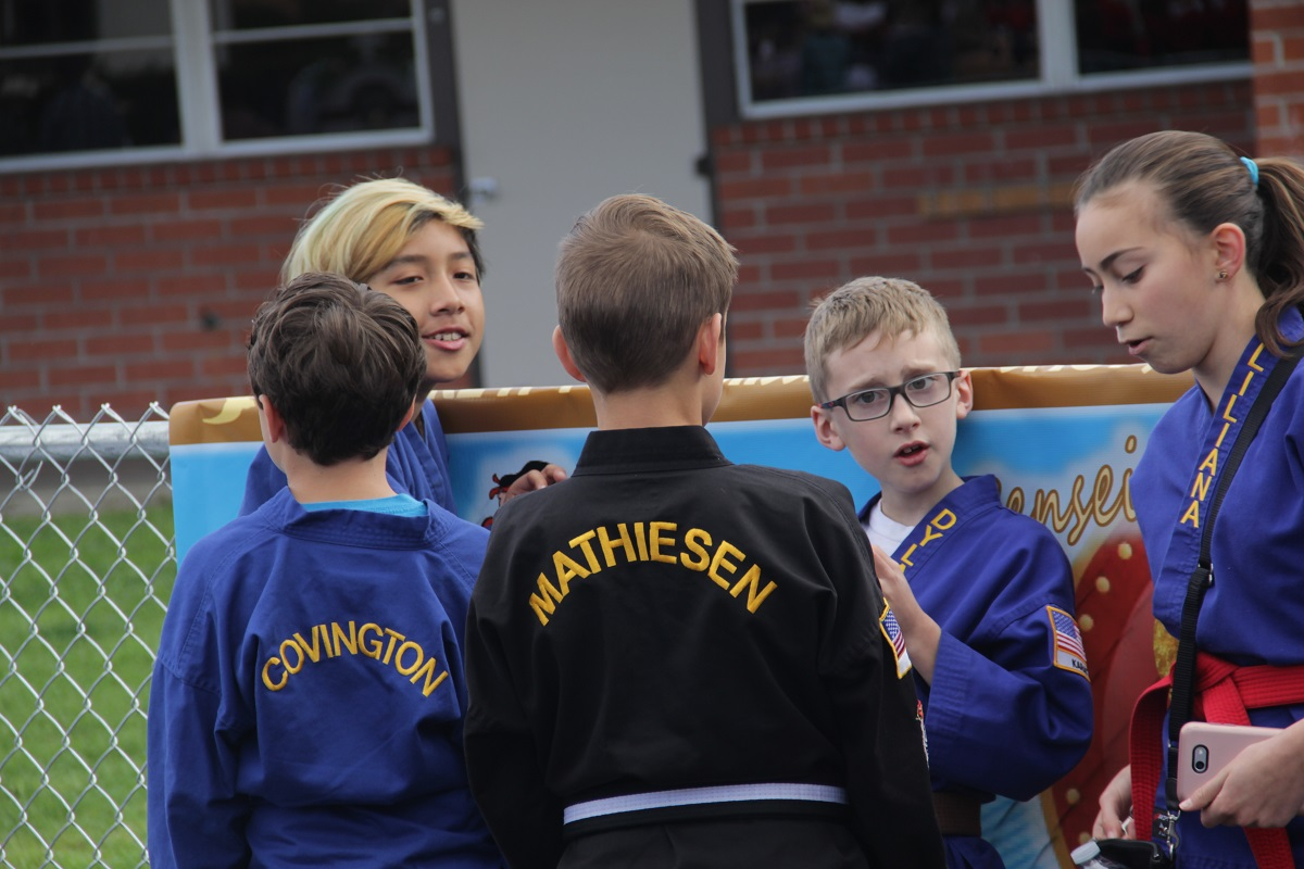 A group of kids with the Zen Dojos Martial Arts Academy huddle around as they wait for the parade to start. Photo: Shawn Raymundo