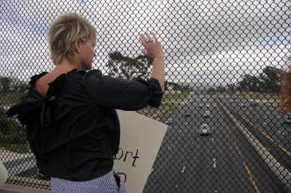 "Traci Arth-Streets, a San Clemente resident, holds up a sign reading ""Freedom of Choice"" on the Camino De Estrella overpass during a Tuesday, May 21 protest against new abortion bans that several states have recently passed. Photo: Shawn Raymundo"