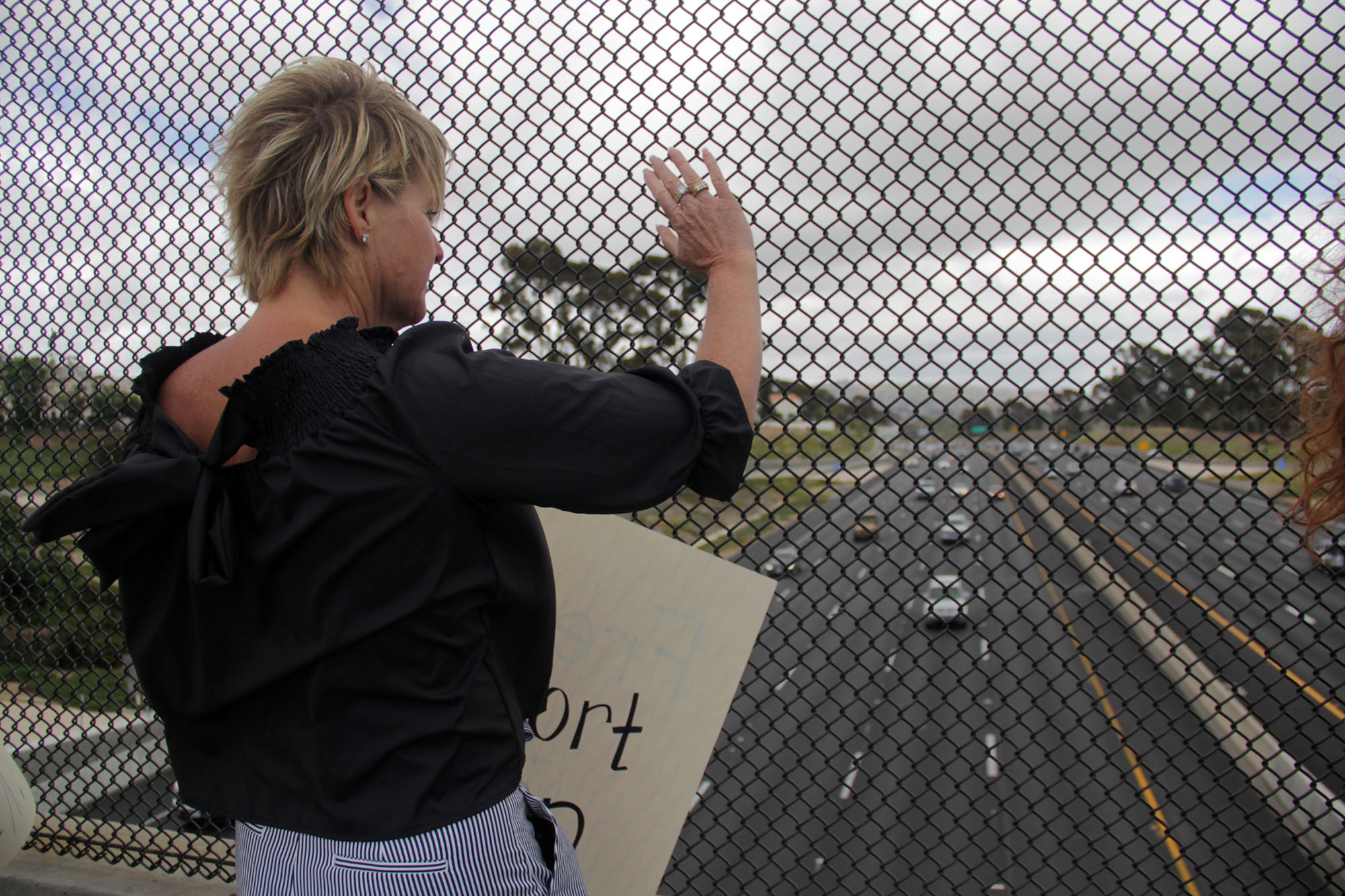"""Traci Arth-Streets, a San Clemente resident, holds up a sign reading """"Freedom of Choice"""" on the Camino De Estrella overpass during a Tuesday, May 21 protest against new abortion bans that several states have recently passed. Photo: Shawn Raymundo"""