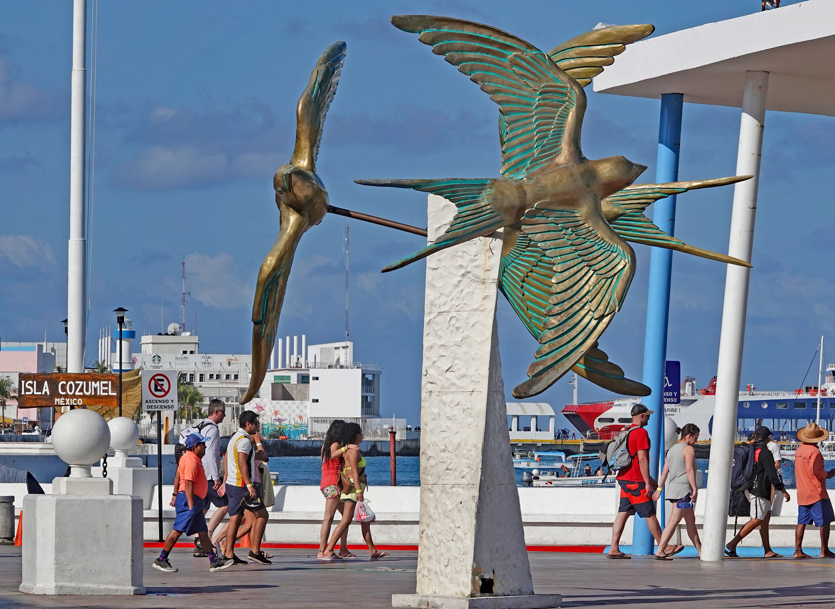 People stroll past Cozumel Island's downtown monument to the island's swallows, while preparing to board ferries to the Mexican mainland, Playa del Carmen. Photo: Fred Swegles