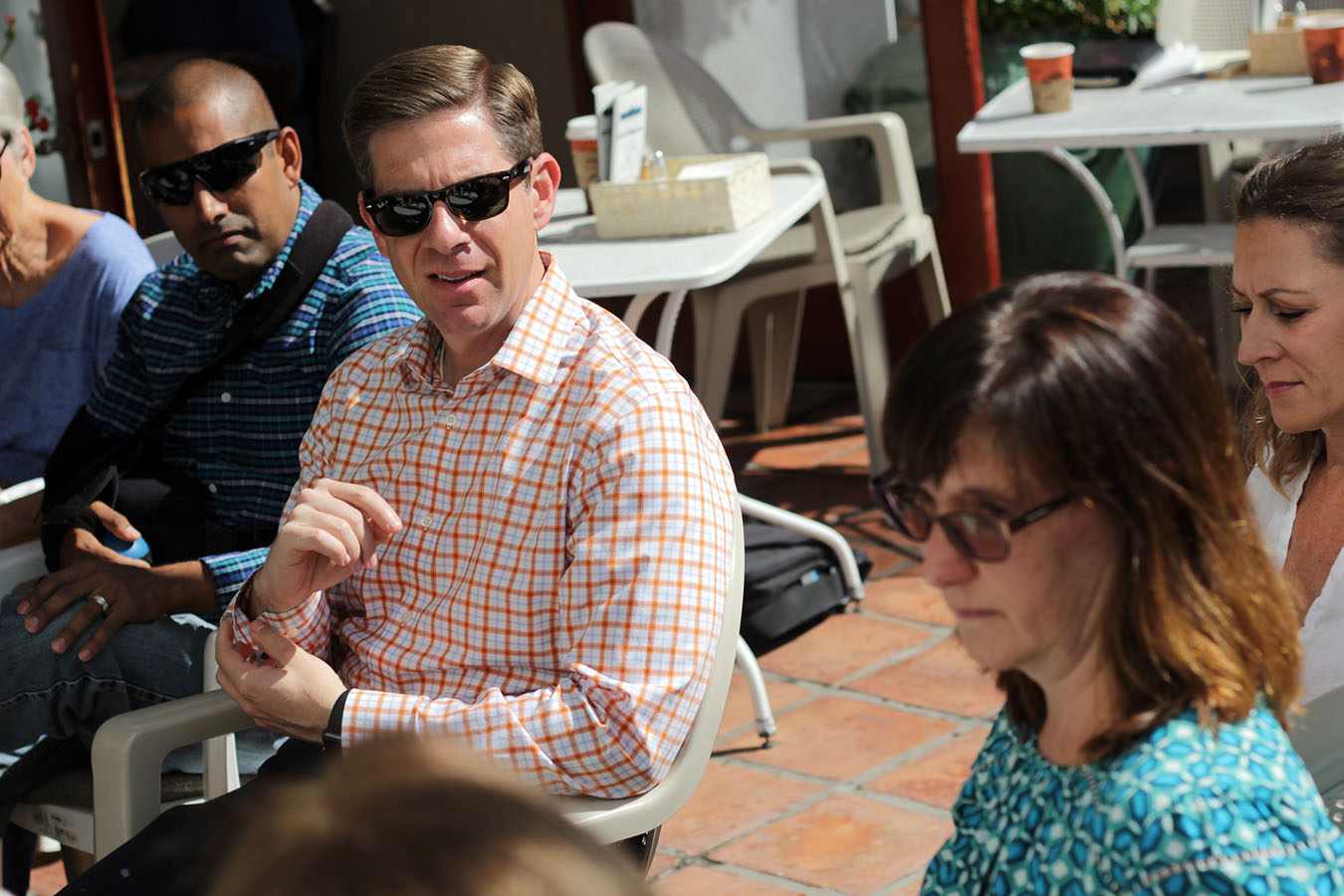 With sun beating down on the patio of Café Calypso in San Clemente, Congressman Mike Levin begins rolling up sleeves while listening to constituents of California's 49th Congressional District on Wednesday, May 29. Photo: Shawn Raymundo