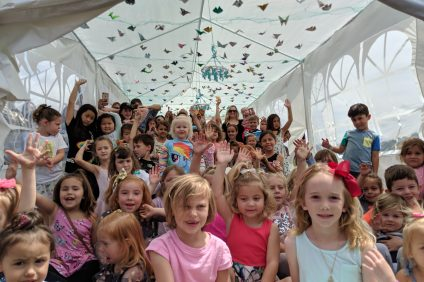Children gather in a tent enclosure for their time with the butterflies. Photo: Courtesy of Peter Dang
