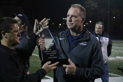 St. Margaret's boys lacrosse coach Glen Miles (right, receiving the 2019 US Lacrosse Orange County championship trophy) stepped down from the position after seven years at the school. Photo: Zach Cavanagh